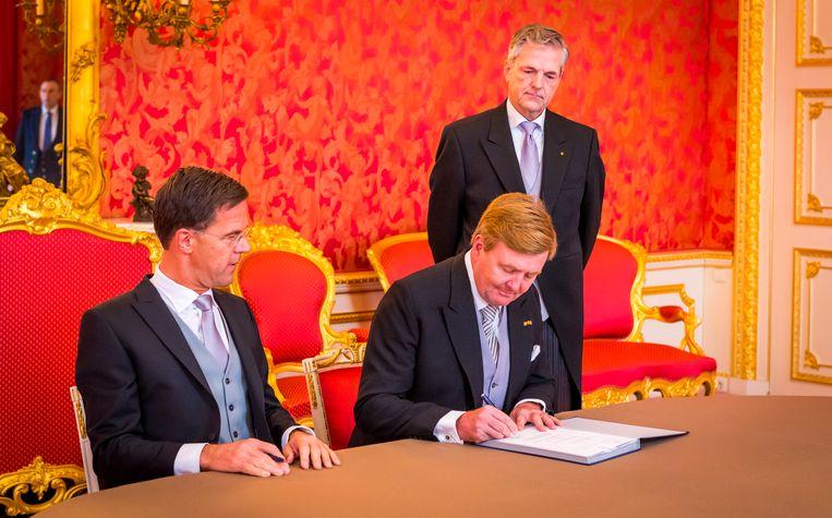 Koning Willem-Alexander en minister-president Mark Rutte tekenen de Koninklijke Besluiten. Beeld anp