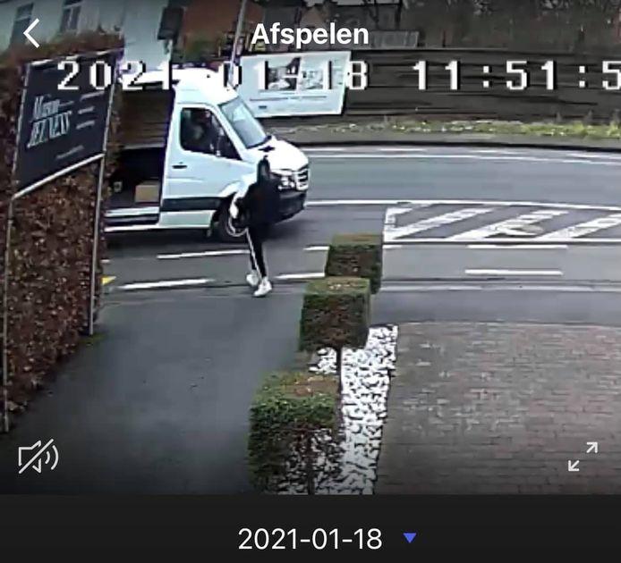 Een dame met mondmasker stapt in de Bruggestraat in Ingelmunster met een geleverd pakje weg. Een Mercedes Sprinter wacht haar op de straat op.