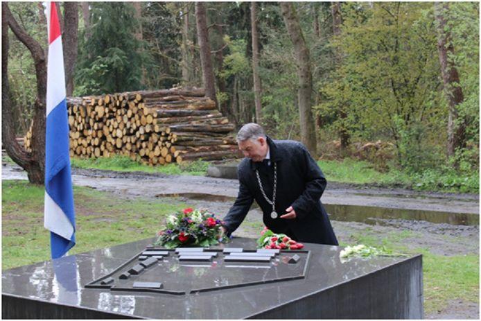 Burgemeester Hans Vroomen legt bloemen op het monument dat herinnert aan het beruchte Kamp Erika.