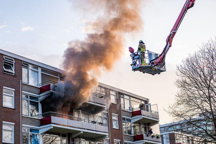 Appartement brandt uit in Tilburg, de brandweer probeert te blussen.