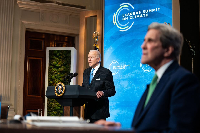 President Joe Biden tijdens de virtuele klimaattop afgelopen week. 'Klimaattsaar' John Kerry luistert mee. Beeld Photo News