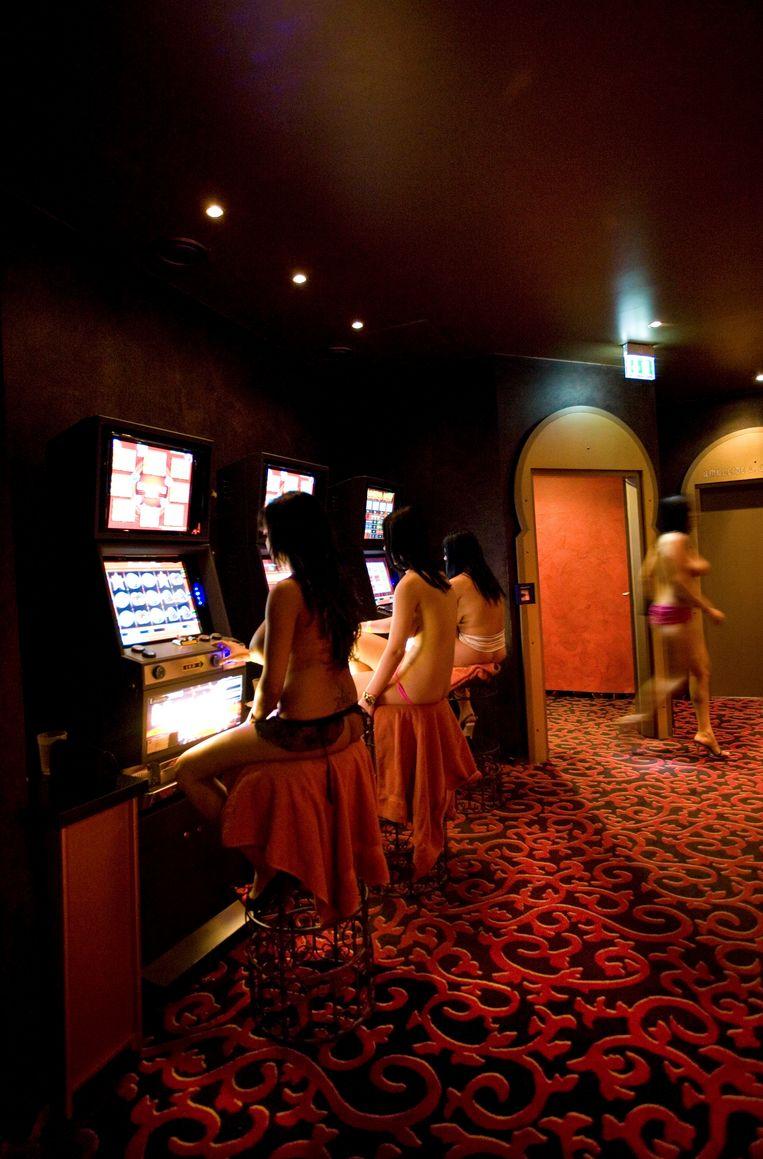 Vrouwen wachten aan de gokmachines op klanten. Van hun pooiers moeten ze zo'n 500 euro per dag verdienen. Beeld Kathrin Harms/laif