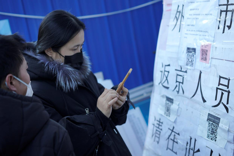 Mensen scannen een QR-code om hun risicoprofiel door te geven terwijl ze Beijing betreden. Beeld REUTERS