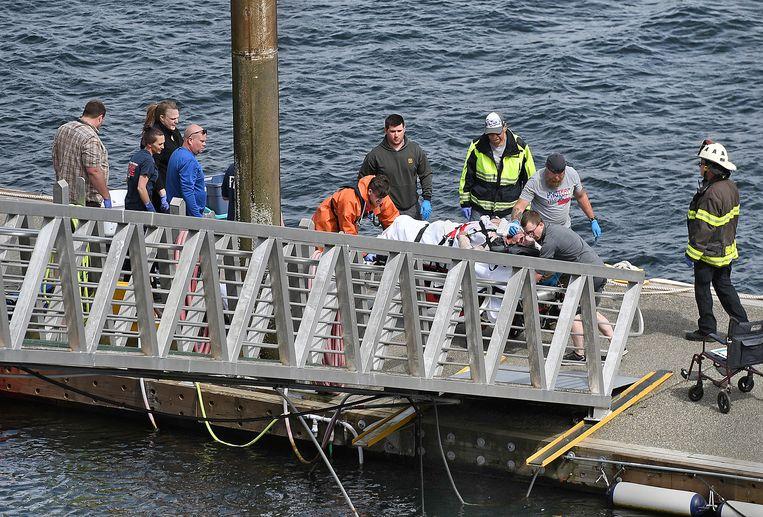 Hulpverleners brengen een gewonde passagier van een van de twee gecrashte vliegtuigen aan wal in Ketchikan, Alaska.