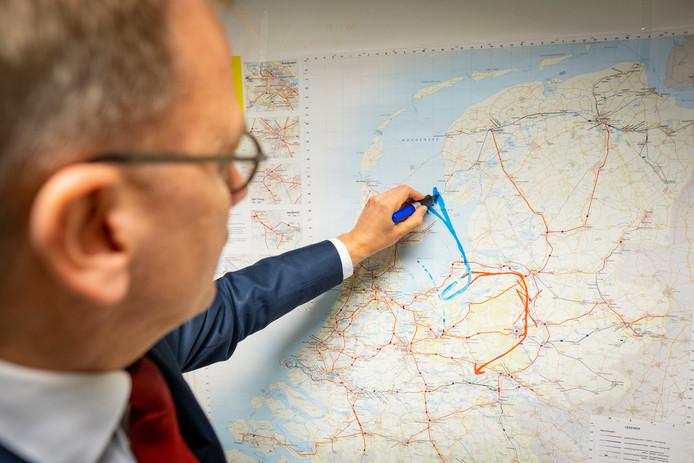 Eppo Bruins van de ChristenUnie tekent op een landkaart de vliegroute die hij vanaf Lelystad Airport voor ogen heeft en die gaat over het IJsselmeer. In het rood de huidige route