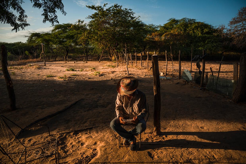 Jose Manuel Gonzalez naast de graven van zijn twee zoons, om het leven gekomen tijdens een gewelddadig conflict over smokkelroutes. Beeld NYT/ADRIANA LOUREIRO FERNANDEZ