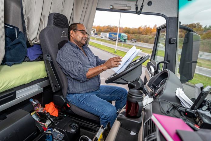 Vrachtwagenchauffeur in zijn cabine van de vrachtwagen langs de snelweg A67 bij Eindhoven.