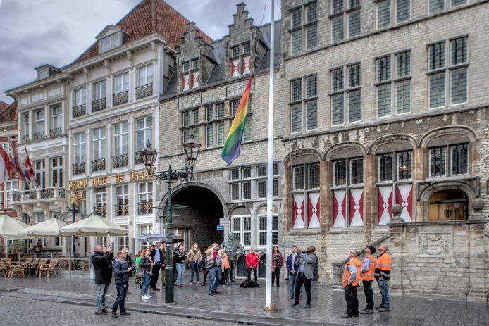 Wethouder Andrew Harijgens hijst de regenboogvlag voor het oude stadhuis op de Grote Markt.