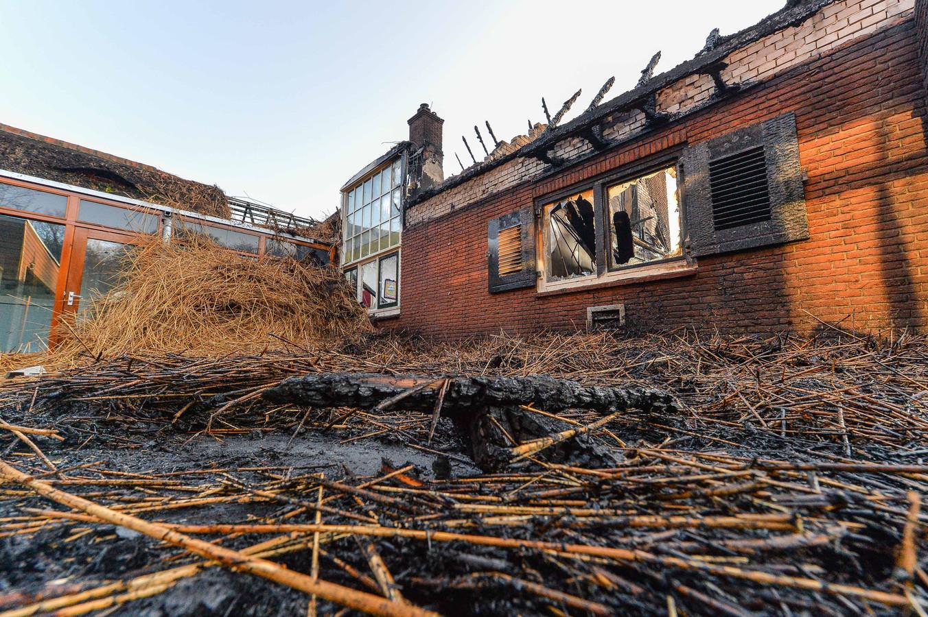 Het door brand verwoeste pand bij zonsopkomst. De verslavingskliniek van het Leger des Heils in Ugchelen ging in vlammen op.