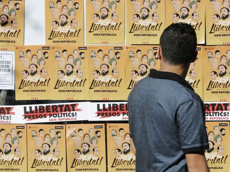 Een man stapt voorbije affiches waarop de vrijlating wordt geëist van acht voormalige leden van de Catalaanse regering.