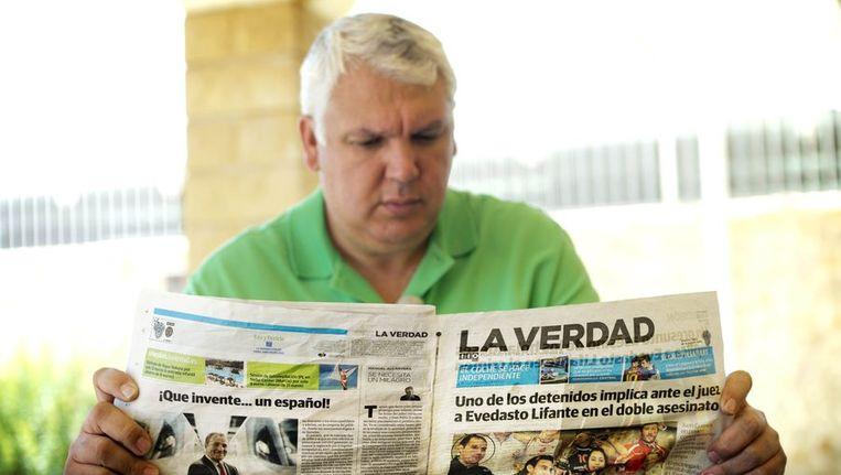 Vedasto Lifante, eigenaar van de volleybalclub waar Ingrid Visser in de jaren 2009 - 2011 heeft gespeeld, leest in de krant La Verdad de berichtgeving over de moord op Visser en haar partner. Beeld anp