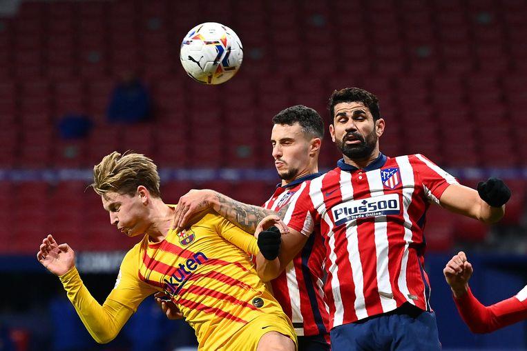 Frenkie de Jong verliest een kopduel van Atlético-aanvaller Diego Costa (rechts) en verdediger Mario Hermoso (midden). Beeld AFP