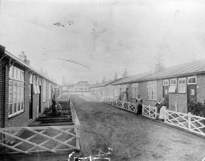 Noodwoningen in Rijnwijk met enkele van de bewoners, kort voor de afbraak in 1928. Links op de achtergrond zien we vaag de Grote of Eusebiuskerk.