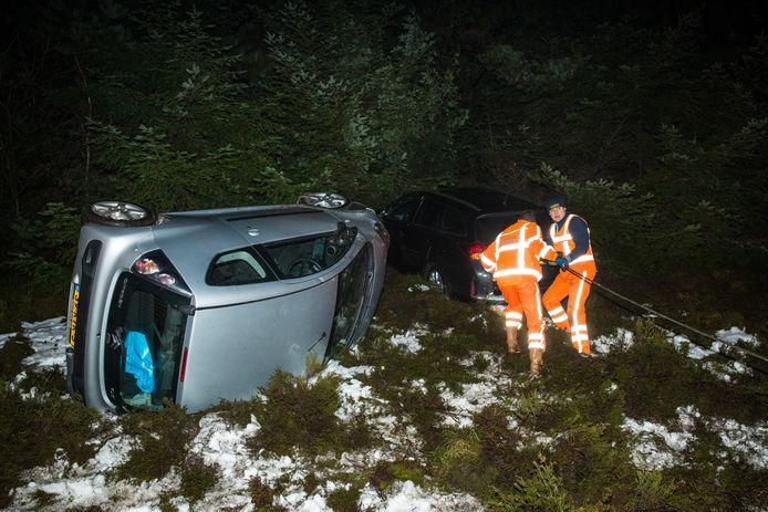 Medewerkers van een bergingsbedrijf halen de eerste van de twee auto's uit de berm van de A50.