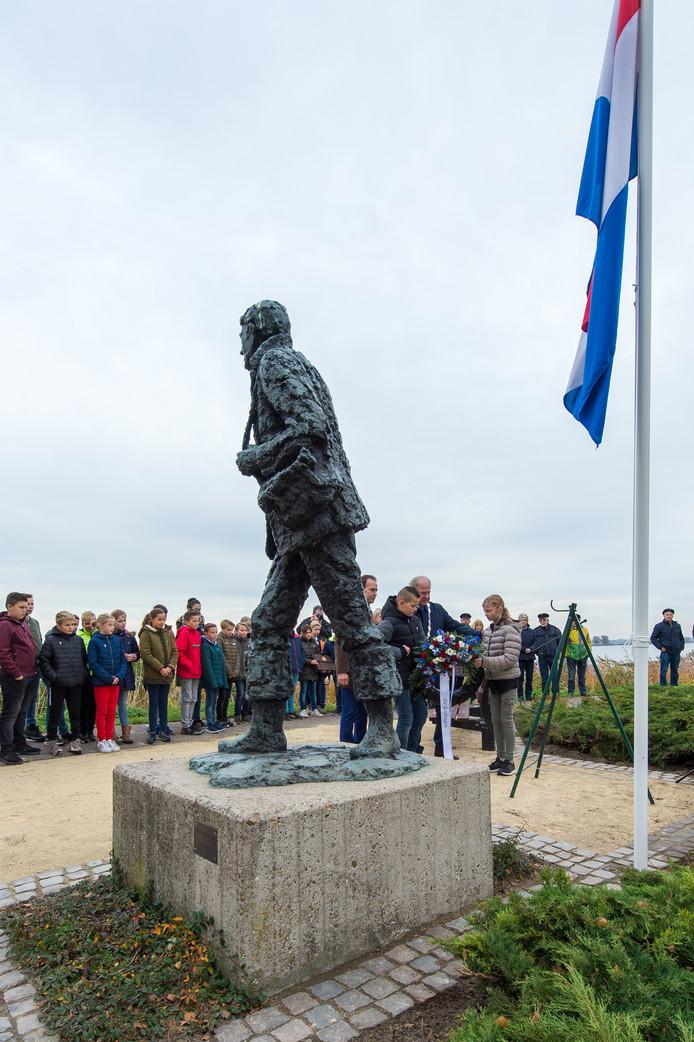 Adoptieoverdracht standbeeld liniecrossers in Lage Zwaluwe. Kinderen leggen bloemen bij het monument. Pix4Profs/René Schotanus