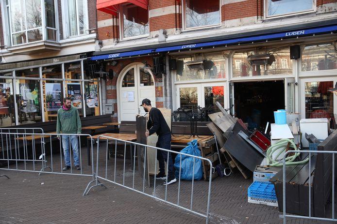 Den Haag Personeel van CafŽ-Restaurant Luden zijn alle terras stoelen en tafeltjes aan het verplaatsen zij beginnen nood gedwongen een afhaalrestaurant eind deze week.  Vanwege het corona virus is de horeca gesloten. Op het plein staan alle terras stoeltjes opgestapeld. foto: ARIE KIEVIT
