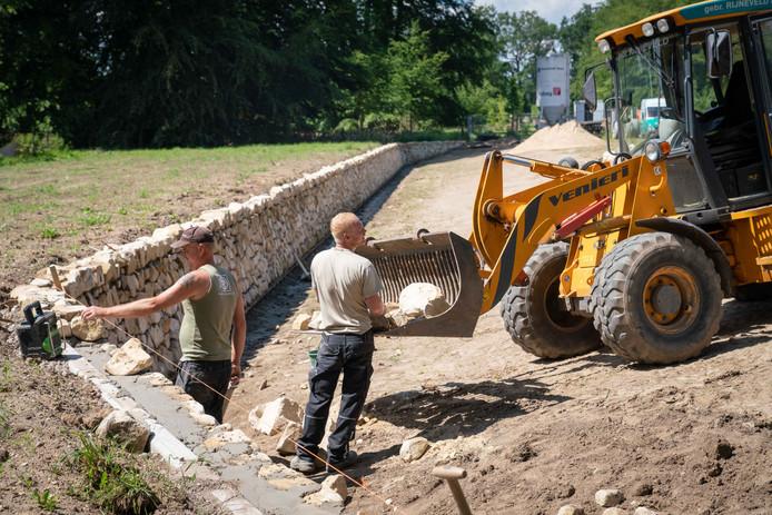 De bouw van de ha-ha. Tegen een betonnen wand worden zandstenen blokken gemetseld.