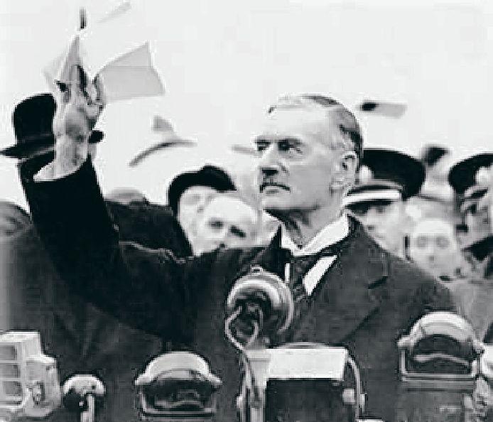 Neville Chamberlain, terug in Londen na zijn ontmoeting met Hitler in 1938 in München, toont zijn getekende overeenkomst met de Duitse dictator: 'I believe it is peace for our time'.