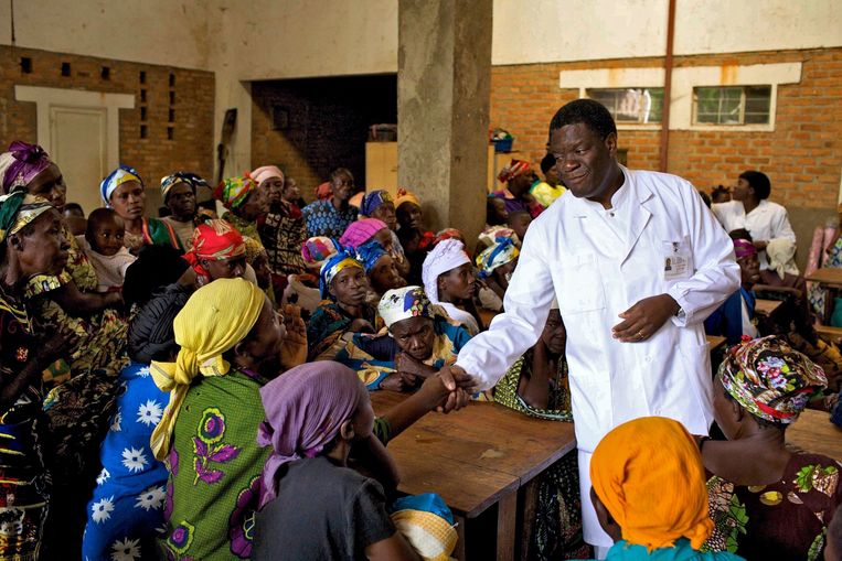 Dokter Denis Mukwege in 2018 tussen vrouwen in Oost-Congo.  Nu loopt zijn leven gevaar.  Beeld EPA