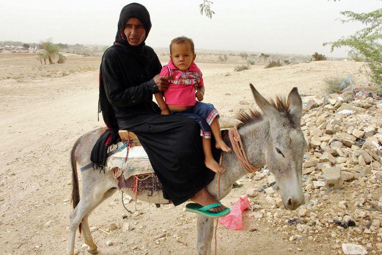 Een vrouw is met haar kind op weg naar een kliniek in Hajjah. Beeld AFP