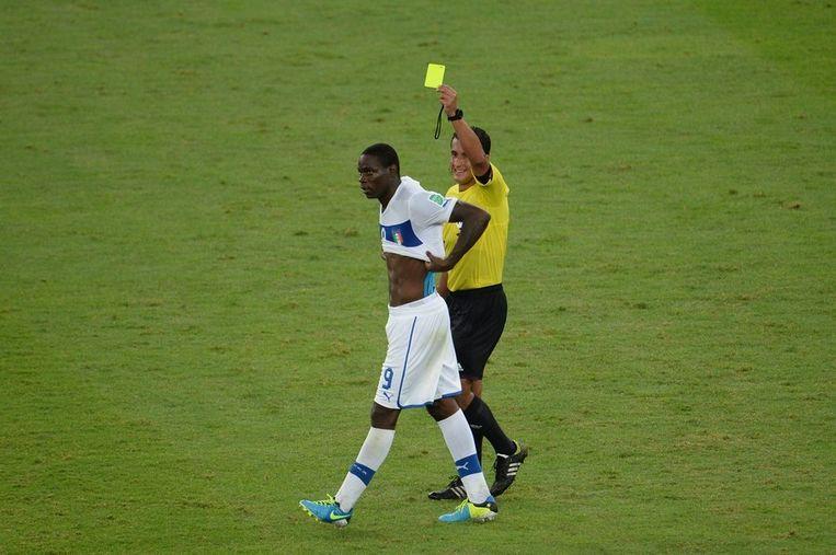Mario Balotelli krijgt geel nadat hij, na zijn treffer tegen Mexico, zijn shirt heeft uitgetrokken. Beeld afp