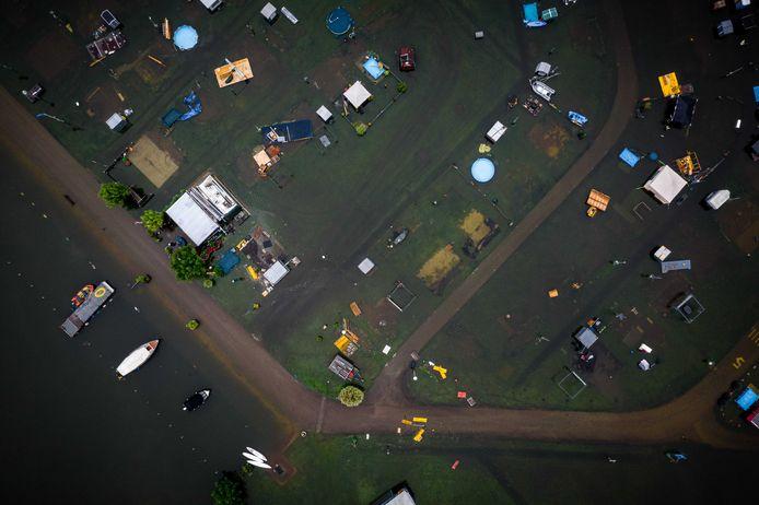 Dronefoto van caravans en campers onder water op camping De Hatenboer in Roermond.