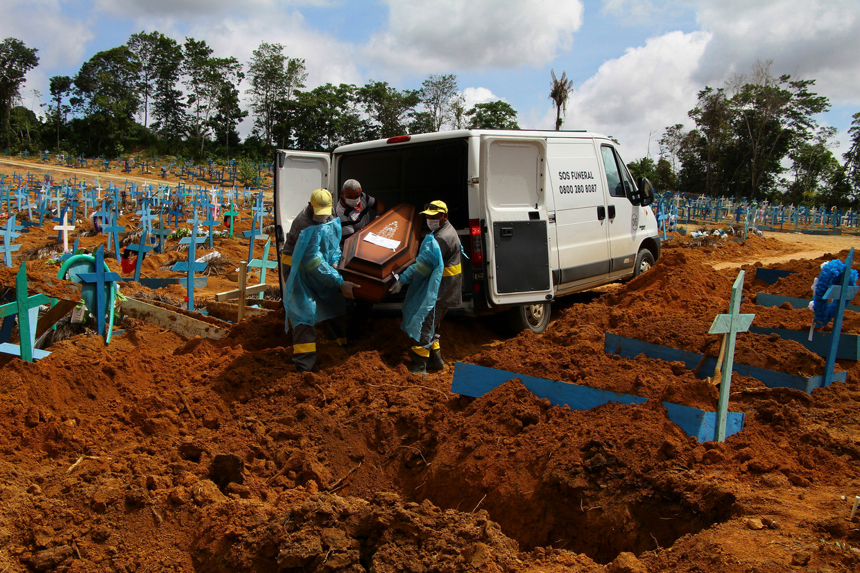 Een coronadode wordt ter aarde besteld in Manaus. De stad in de Braziliaanse deelstaat Amazonas kampt met een groot aantal besmettingen met een nieuwe variant van het coronavirus. Beeld Edmar Barros / AP
