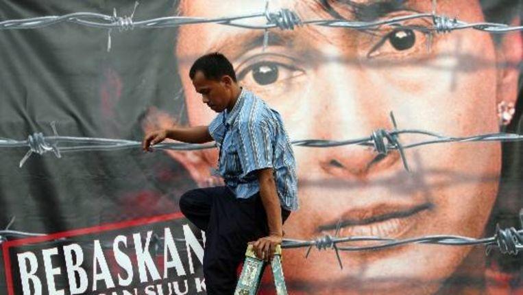Een man hangt een gigantische poster van de Burmese oppositieleidster Aung San Suu Kyi op bij de Britse ambassade in Jakarta, Indonesië. (EPA) Beeld