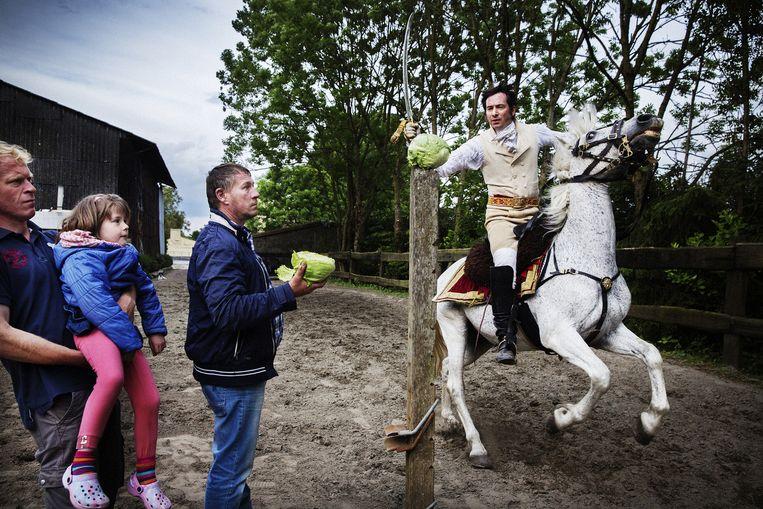 Simon, te paard, bekwaamt zich met kroppen sla in het afhakken van hoofden. Beeld Tim Dirven
