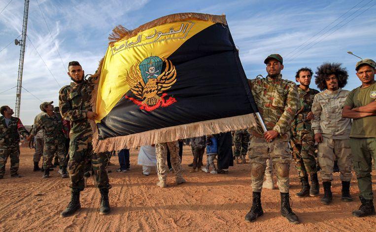 Leden van de 'Speciale Krachten' van het LNL, het Libische Nationale Leger van generaal Haftar, poseren met hun vlag. Beeld AFP