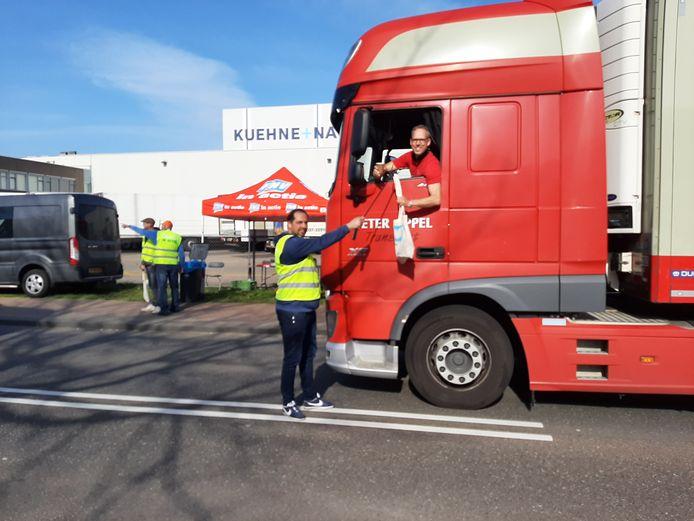 Karim Janssen, kaderlid van de FNV, overhandigt een voorbijkomende collega-chauffeur een tasje met actiemateriaal.