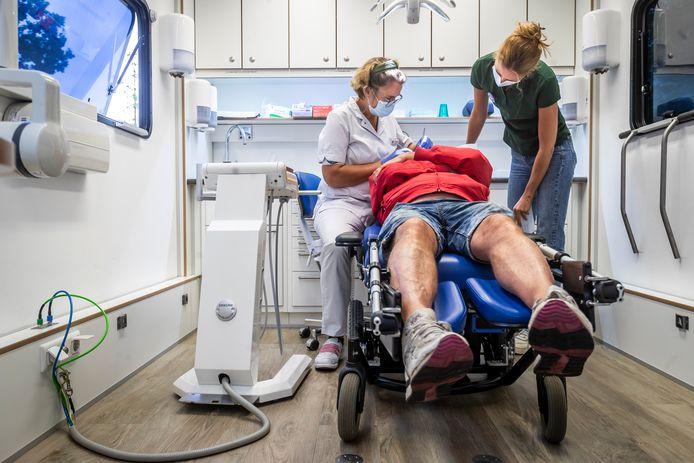 Op het terrein van de Agnus Dei kerk in Waalre staat een tandartskaravaan. Mensen die een beroep moeten doen op de voedselbank kunnen daar een gratis noodbehandeling krijgen. Tandarts Didi Landman helpt een cliënt.