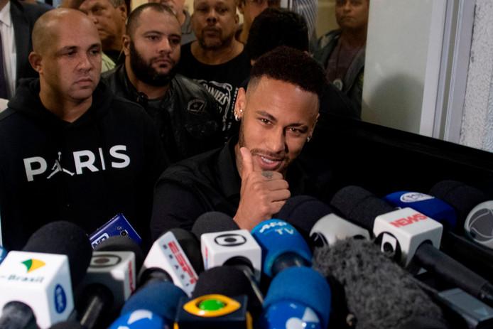 Neymar bij het verlaten van het bureau, omgeven door tientallen verslaggevers en cameraploegen.