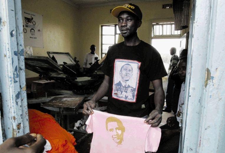 Een man showt voor zijn zeefdrukkerij in Nairobi T-shirts met een opdruk van Barack Obama. (FOTO REUTERS) Beeld