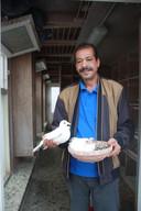 Duivenverzorger Hamid Bhayaje met een nest duiven.