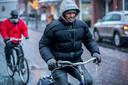 Nederland,  Schijndel, sneeuw op de markt bij de kerk en Glazen Boerderij. Foto fietsers op de hoofdstraat bij de Gllazen Boerderij