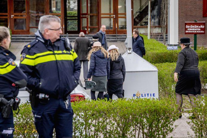 Politieagenten en kerkgangers op Goede Vrijdag bij de Mieraskerk in Krimpen aan den IJssel.