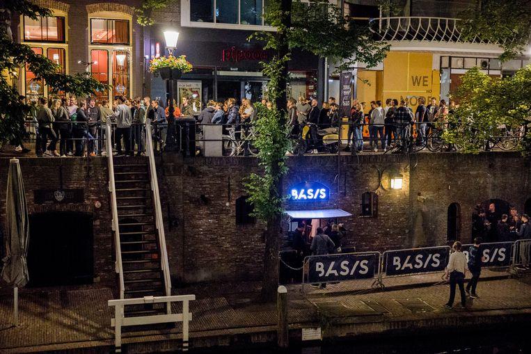 Een lange rij wacht zaterdagavond om te worden toegelaten tot club Basis, beter bekend als de Technobunker van Utrecht. 'Ik heb er zin in, fuck it, ik wil uit m'n hoofd, de wereld in.' Beeld Arie Kievit