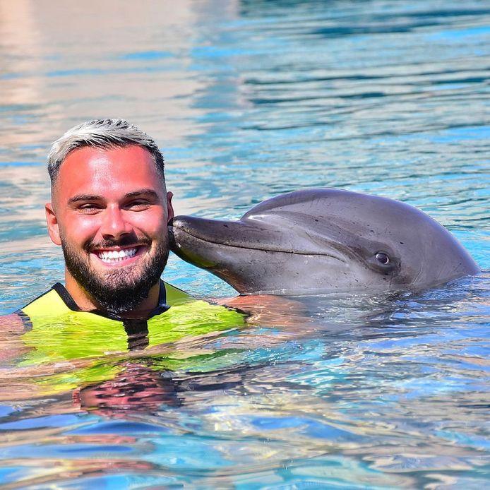 Influencer PA7 poseert met een dolfijn in Dubai. Hij wordt ervan beschuldigd 5,8 miljoen euro aan coronasteun te hebben verduisterd.