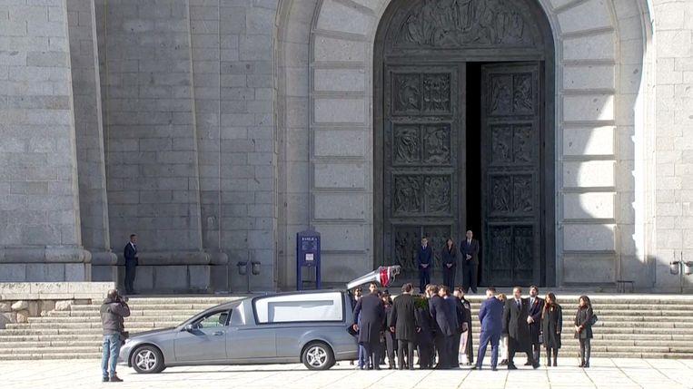 Familieleden plaatsen buiten de monumentale Vallei der Gevallenen de kist met het lichaam van dictator Franco in een lijkwagen. Beeld via REUTERS