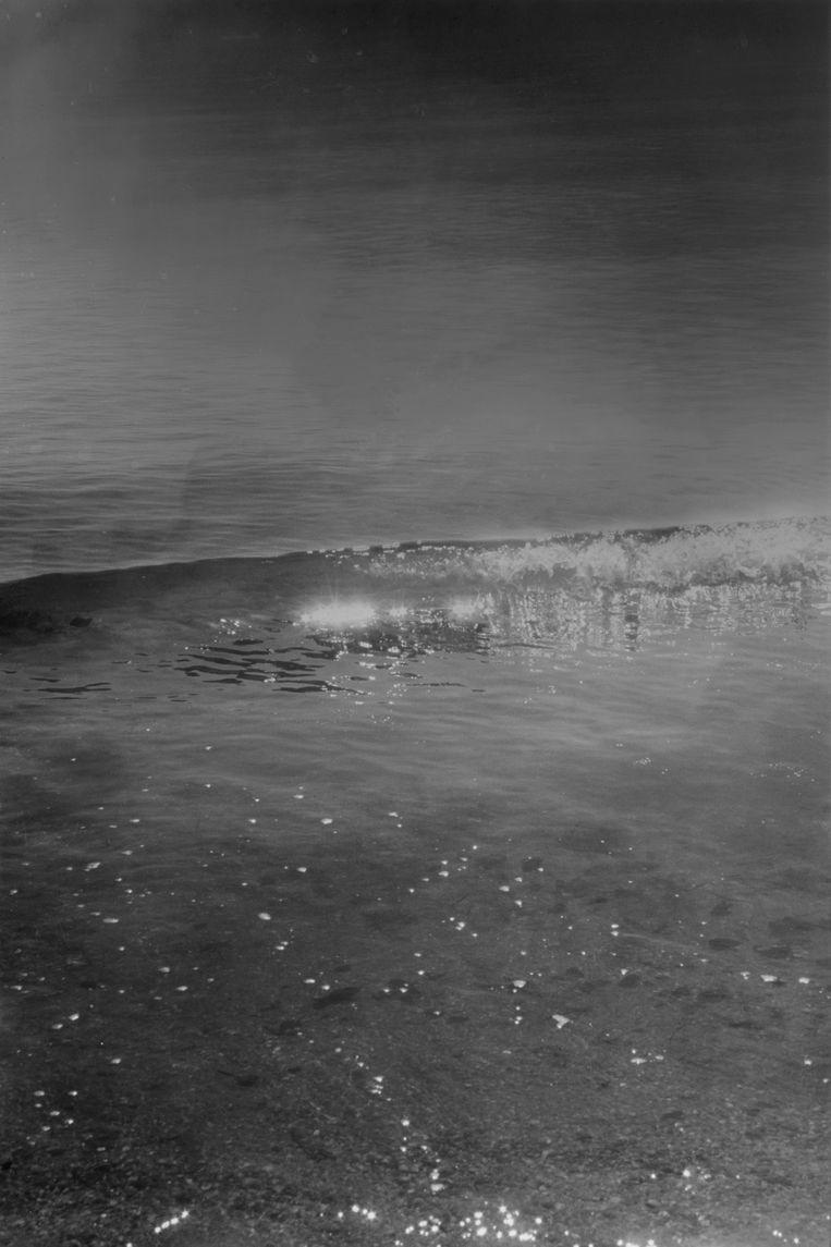 Een golf, stilgelegd nét op het moment dat hij omslaat, met glinstering van de zon op het water. Beeld rv © Dirk Braeckman / Courtesy of Zeno X Gallery, Antwerp