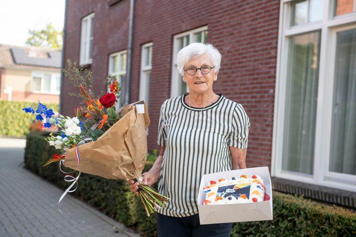 Gerda Knobben-Bouwhuis met taart en bloemen. Het lintje wordt later dit jaar opgespeld.