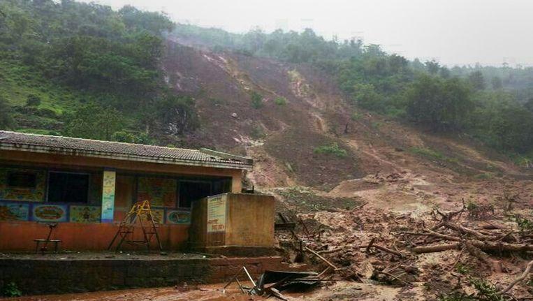 Een modderstroom omringt een gebouw in het dorpje Malin. Beeld BELGA