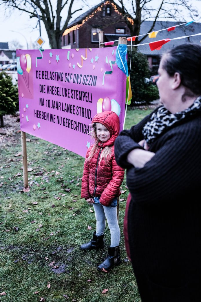 Kristel de Waal met een van haar kinderen bij een protestbord.