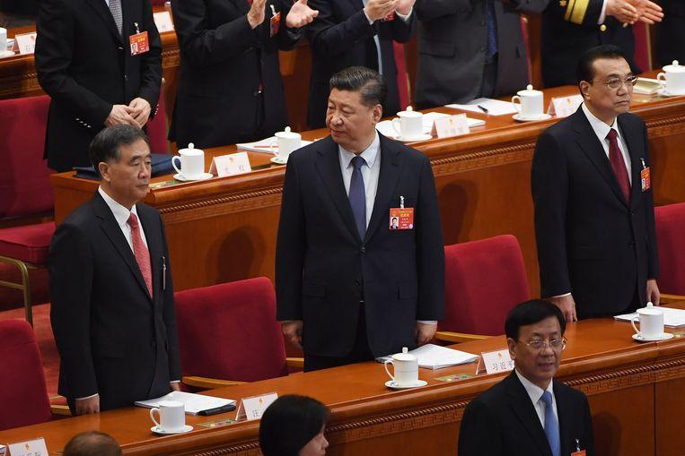 China's President Xi Jinping wacht op de opening van het congres. Hij staat tussen premier Li Keqiang (rechts) en de machtige man in het Politbureau Wang Yang.  Beeld AFP