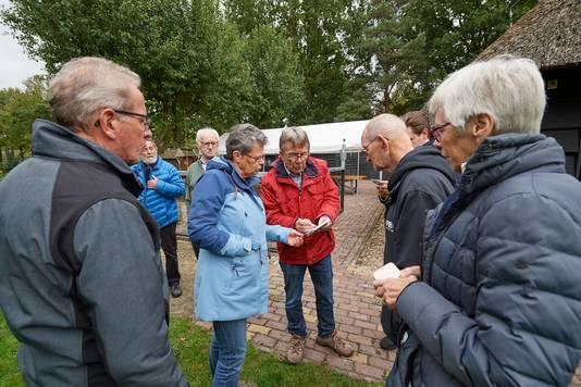 Voorzitter Hans van Sleuwen (midden, rode jas) ontvangt verontruste vrijwilligers. Het museum heeft zo'n 75 vrijwilligers.