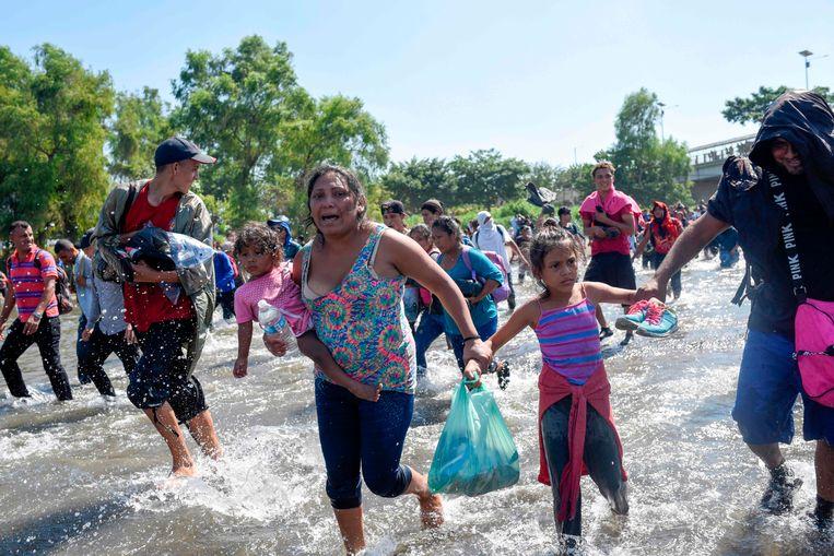 Honderden migranten, de meeste afkomstig uit Honduras, rennen de grensrivier Suchiate over richting Mexico.  Beeld AFP