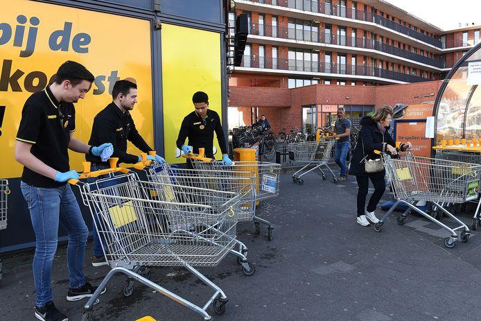 Medio maart dit jaar, net na de uitbraak van het coronavirus. Medewerkers van de Jumbo in Cuijk ontsmetten de winkelwagens voor de klanten.