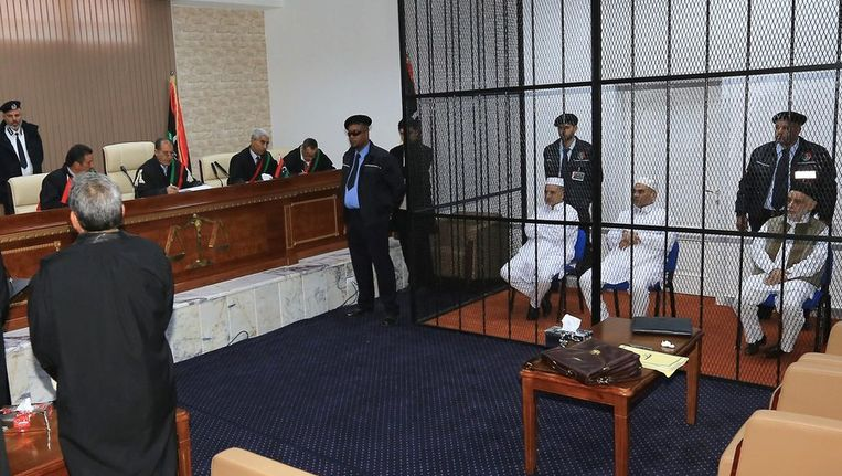 Van rechts naar links: Baghdadi al-Mahmudi, Mabrouk Zhmul) and Amer Saleh Tervas onder bewaking in de rechtbank in Tripoli. Beeld afp