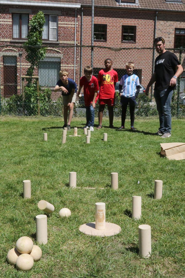 Enkele kinderen spelen 'Leeuwentoren', ontworpen en bijna volledig handgemaakt door leraar Stefaan Vanoplynes (rechts).